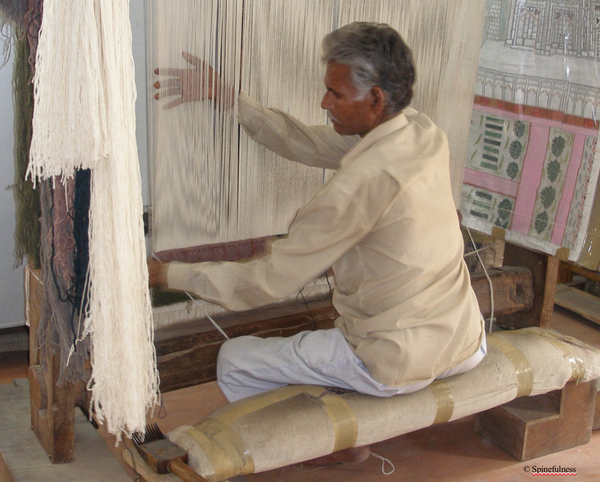 Man sitting straight and working at loom
